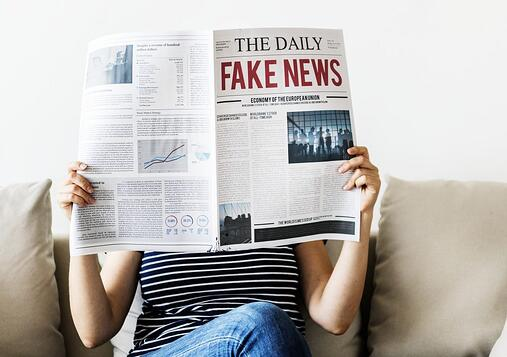 person reading fake news in the newspaper