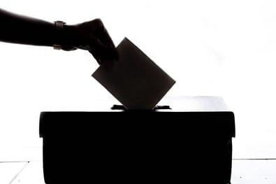 a voting ballot going into a box